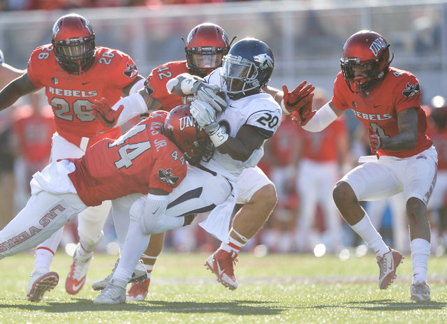 Nevada Wolf Pack running back James Butler (20) is brought down by UNLV Rebels defensive back Kenny Keys (44) during the UNLV Nevada football game at Sam Boyd Stadium in Las Vegas on Saturday, Nov ...