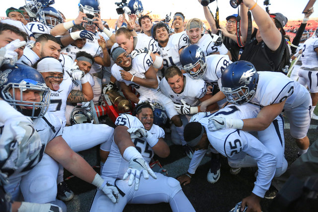 The Nevada Wolf Pack swarms the Fremont Cannon after beating UNLV 45-10 at Sam Boyd Stadium in Las Vegas on Saturday, Nov. 26, 2016. (Brett Le Blanc/Las Vegas Review-Journal) Follow @bleblancphoto