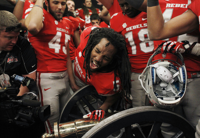 UNLV's Frank Crawford (5) leans over to touch the Fremont Cannon as his teammates celebrate their victory over UNR at Mackay Stadium in Reno on Oct. 26, 2013. (Jason Bean/Las Vegas Review-Journal)