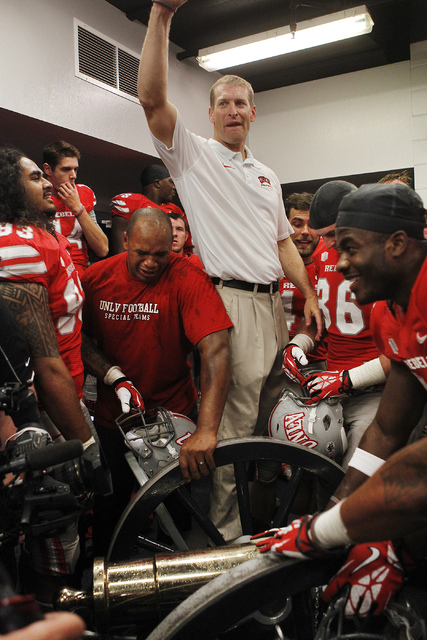 Head Coach Bobby Hauck and his UNLV players rejoice with the Fremont Cannon as they celebrate their victory over UNR at Mackay Stadium in Reno on Oct. 26, 2013. (Jason Bean/Las Vegas Review-Journal)