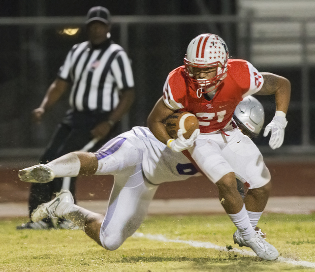 Liberty's Darion Acohido (21) fights for extra yardage with a Silverado defender on his back during the Sunrise Region semifinal game on Thursday, Nov. 10, 2016, at Liberty High School in Henderso ...