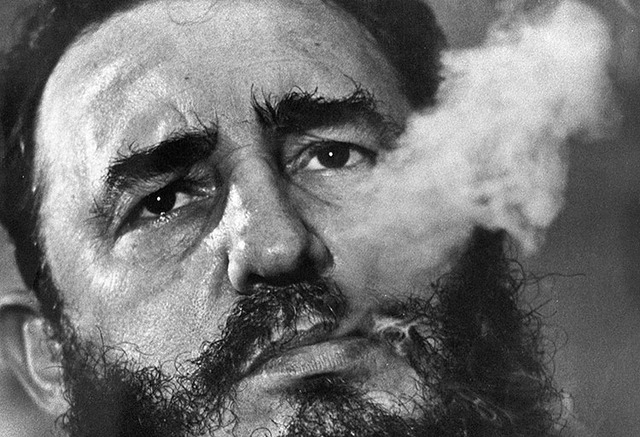 Cuban Prime Minister Fidel Castro exhales cigar smoke during an interview at his presidential palace in Havana, Cuba, in 1985. (AP Photo/ Charles Tasnadi, File)