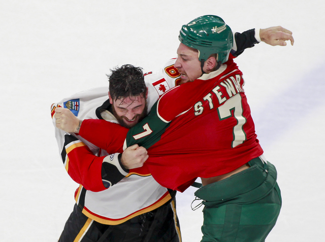 Calgary Flames defenseman Deryk Engelland, left, and Minnesota Wild right wing Chris Stewart (7) fight during the first period of an NHL hockey game, Tuesday, Nov. 15, 2016, in St. Paul, Minn. (AP ...
