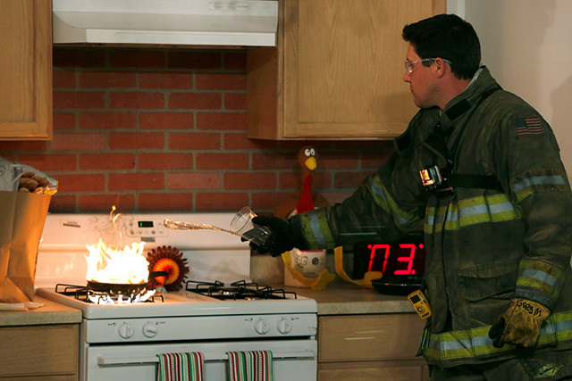 A firefighter demonstrates the incorrect method of putting out a stovetop fire with water at a Consumer Product Safety Commission safety demonstration in Rockville, Maryland. (Gary Cameron/Reuters)