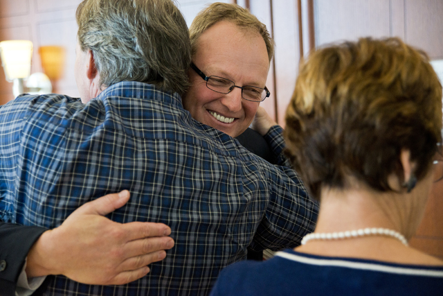 Prosecutor Frank Coumou, right, embraces William Smith after court proceedings regarding the 2009 murder of Robin Lesley Jenkins by David Frostick at the Regional Justice Center in downtown Las Ve ...