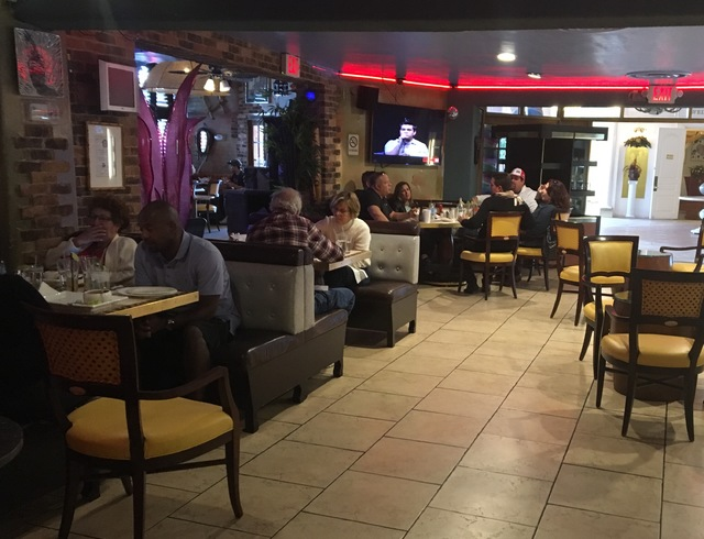 Customers sitting in the bakery section of Florida Cafe Cuban Bar & Grill inside The Shalimar Hotel on Saturday, Nov. 26, 2016, discuss the death of former Cuban President Fidel Castro. (Pasht ...