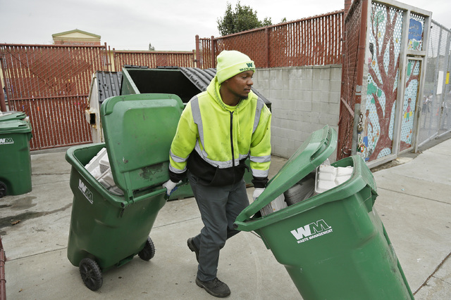 Apprentice garbage man Corey Lever collects trash outside a school in Oakland, Calif. (Eric Risberg/AP)