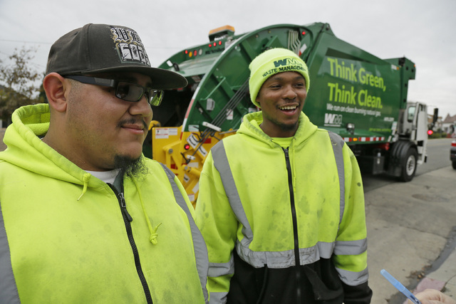 Apprentice garbage men Will Montolla, left, Corey Lever, right, talk about their work during a stop outside a school in Oakland, Calif. (Eric Risberg/AP)