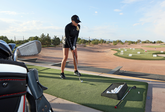"Ladies Professional Golf Association's Natalie Gulbis lines up a shot while playing ""Golf Blackjack"" during a grand opening event featuring a new flight deck and custom-fitting l ..."