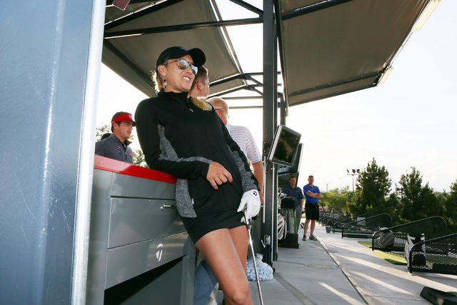 "Ladies Professional Golf Association's Natalie Gulbis watches her competitor take his turn at ""Golf Blackjack"" during a grand opening event featuring a new flight deck and custom-fitting lab at Ta ..."