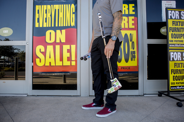 A Golfsmith customer hold's his newly gripped golf clubs outside of the closing store located in downtown Summerlin, 2315 Summa Dr #1b, Wednesday, Nov. 9, 2016, in Las Vegas. Elizabeth Page Brumle ...