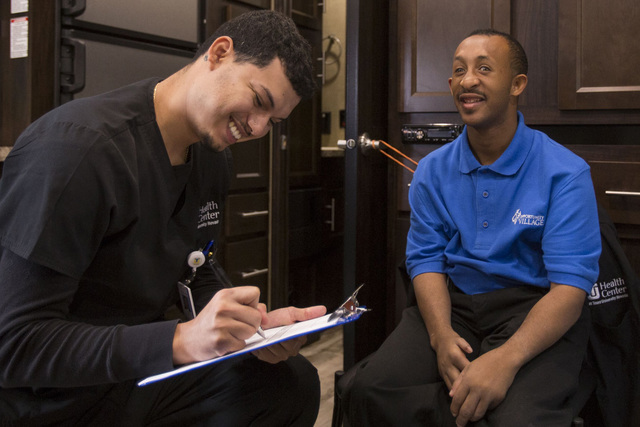 Touro University Health Center employee Cristian Dones, left, laughs with Opportunity Village custodian Reginald Daniel, 28, inside Touro's new mobile healthcare clinic in the parking lot of the O ...