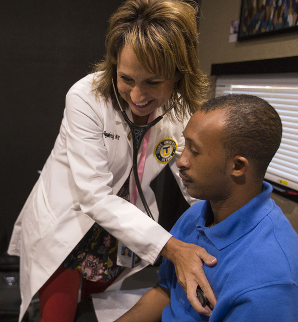 Touro University Nurse Practitioner Sara Dougherty performs a medical exam on Opportunity Village custodian Reginald Daniel, 28, inside Touro's new mobile healthcare clinic in the parking lot of t ...