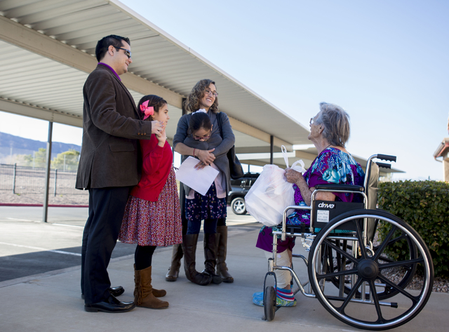Betty Hurd, right, holds a full Thanksgiving meal that was delivered to her by the Aguirre family, volunteers from St. Thomas More Catholic Community on Thursday, Nov. 24, 2016, in Henderson. Eliz ...