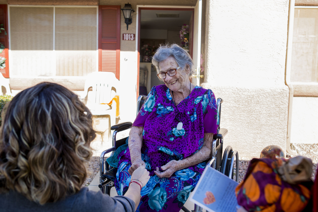 Betty Hurd, center, holds the hand of Maria Aguirre, a St. Thomas More Catholic Community volunteer, while Aguirre delivers Hurd a full Thanksgiving meal to her home, Thursday, Nov. 24, 2016, Hend ...