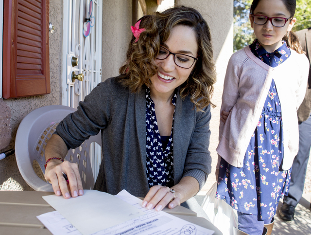St. Thomas More Catholic Community volunteer Maria Aguirre, left, writes a note to a senior citizen receiving a full Thanksgiving meal, as her daughter, Isabella Aguirre, 10, looks on Thursday, No ...