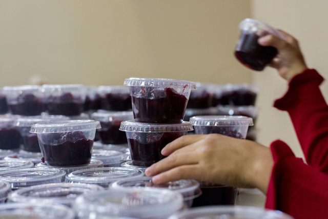 A young volunteer organizes cranberries to be distributed to other volunteers that will deliver full Thanksgiving meals to the homes of senior citizens, Thursday, Nov. 24, 2016, at St. Thomas More ...