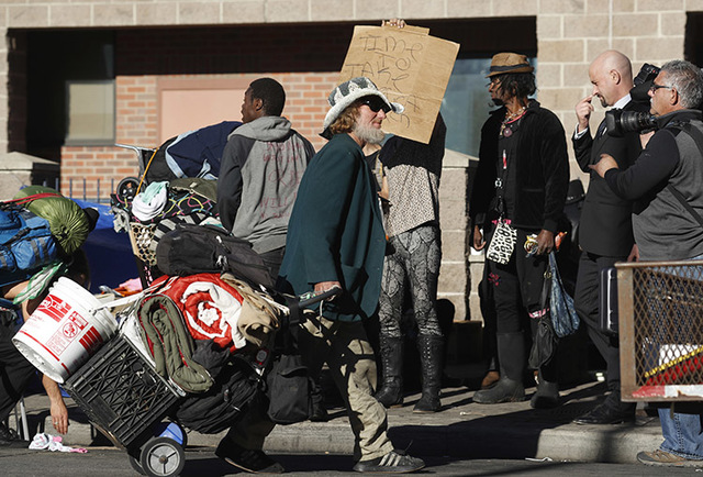 An unidentified man drags his belongings away during a sweep of homeless people who were living on the walks surrounding a shelter near the baseball stadium Tuesday, Nov. 15, 2016, in downtown Den ...