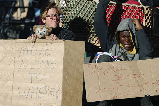 Shannon Wolf, left, and a man who identified himself as King Reality hold homemade placards to protest during a sweep of homeless people who were living on the walks surrounding a shelter near the ...