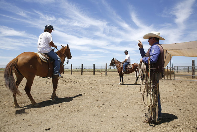 Joe Misner, right, manager of the Wild Horse Program, advises inmates Dax Poplawski, left, and Chris Culcasi at the Rio Cosumnes Correctional Center in Elk Grove, Calif.  (AP Photo/Rich Pedroncelli)