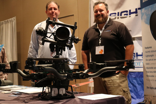 Jason Drotman of System Integration Plus, left, and  William O'Donnell, vice president of technology at AviSight, pose for a photo with a drone carrying their Ranger 30x optical zoom camera at t ...
