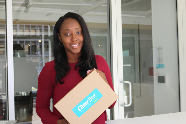 Tamar Lucien,  CEO and cofounder of Mental Happy, displays a cheer box. The box contains a gratitude jar, a journal for positive thoughts, an adult coloring book, and other items meant to ease anx ...
