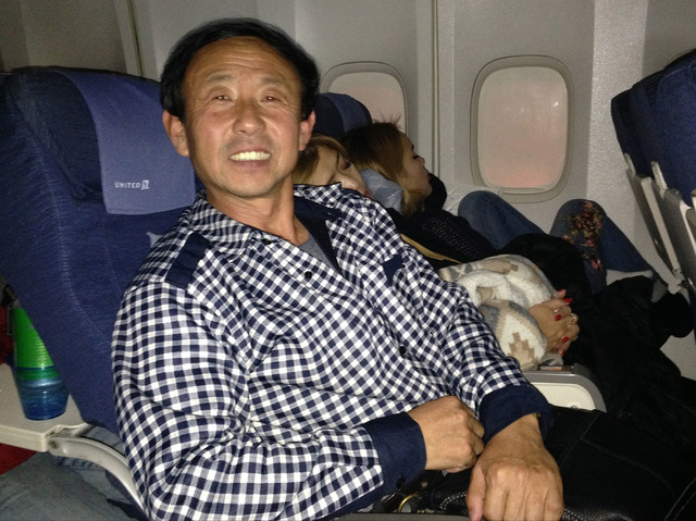 Bingcai Deng, a Chinese man, is aboard a United Airlines flight from San Francisco to Beijing, Monday, Nov. 29, 2016. He is returning to Weihai, a city in eastern Shandong province, China, after v ...