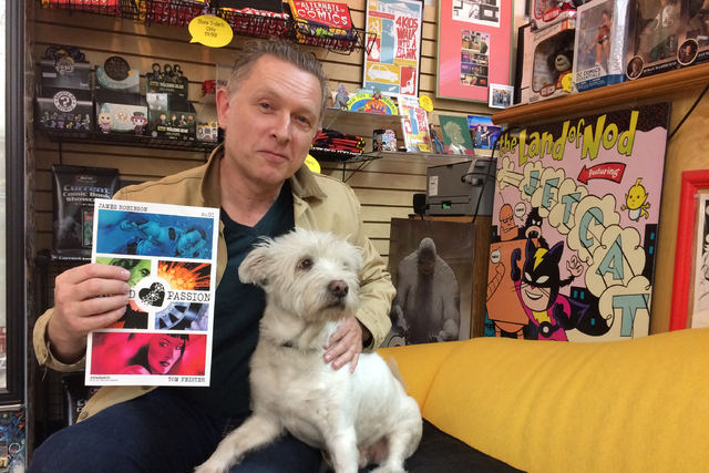 """Comic book writer James Robinson hangs out at Alternate Reality Comics with two of his favorite things, a copy of """"Grand Passion"""" No. 1 and his dog Rex."""
