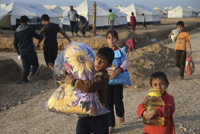 Displaced Iraqi boys, who fled from Mosul with their families, carry food and other aid supplies at a camp for internally displaced people in Hassan Sham, east of Mosul, Iraq. (Hussein Malla/AP)