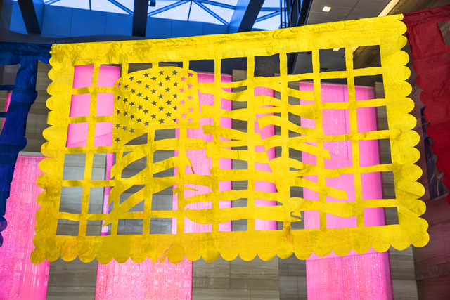 """An American flag waves from a banner featured in artist Justin Favela's """"Patrimonio,"""" on display at Las Vegas City Hall. Benjamin Hager/Las Vegas Review-Journal"""