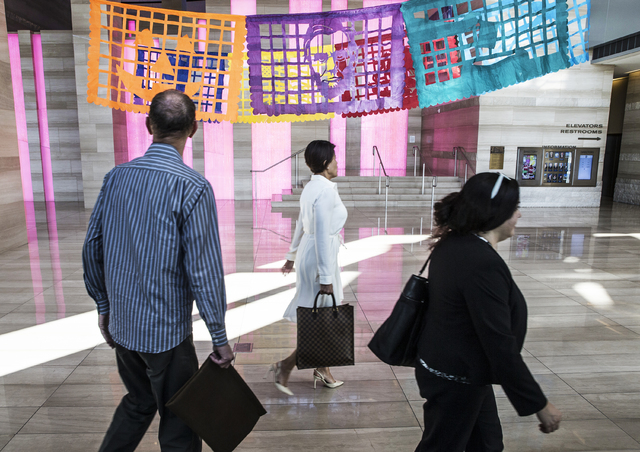 """Visitors at Las Vegas City Hall pass by Justin Favela's art exhibit """"Patrimonio,"""" which continues on display through Dec. 15. Benjamin Hager/Las Vegas Review-Journal"""