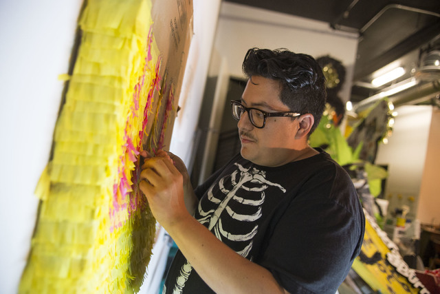 Artist Justin Favela glues strips of hand-cut tissue paper onto cardboard while working on a commissioned piece inside his studio at the Juhl in downtown Las Vegas. Richard Brian/Las Vegas Review- ...