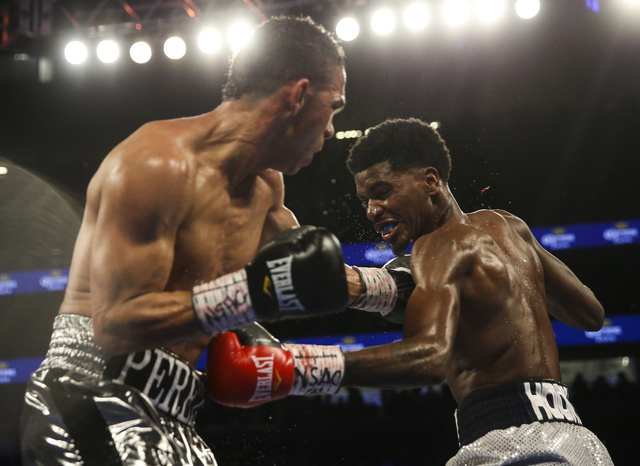 Darleys Perez, left, and Maurice Hooker trade punches during their junior welterweight boxing match at T-Mobile Arena in Las Vegas on Saturday, Nov. 19, 2016. Chase Stevens/Las Vegas Review-Journa ...
