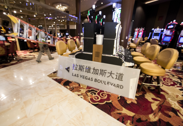 A sign with English and Chinese languages sits on the floor while a worker passes by in the Lucky Dragon hotel-casino, 300 W. Sahara Ave., on Friday, Nov. 18, 2016. Las Vegas' newest casino, which ...