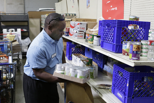 Derrick Felder, facility and nutrition manager at Lutheran Social Services of Nevada (LSSN), stores canned vegetables on the pantry shelves at LSSN, Wednesday, Oct. 26, 2016, in Las Vegas. Bizuaye ...