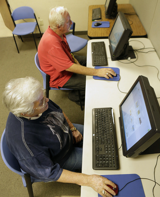 Jess Parker, left, and Mary Lu Tieman, both volunteers and clients at Lutheran Social Services of Nevada (LSSN), use a computer to order items from nonprofit's food pantry at LSSN, Wednesday, Oct. ...