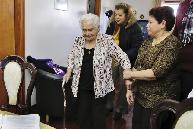 America Maria Hernandez, 99, left, is aided by her granddaughter Monica Martinez, center, and daughter Ana Martinez as she prepares to take the Naturalization Oath of Allegiance, Wednesday, Nov. 2 ...
