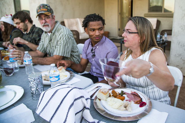 In this Thursday, Nov. 24, 2016 photo, Jamal Hinton, center, and Wanda Dench, right, and her family and friends, have Thanksgiving dinner at Wanda's home, in Mesa, Ariz.  (Tom Tingle/The Arizona R ...