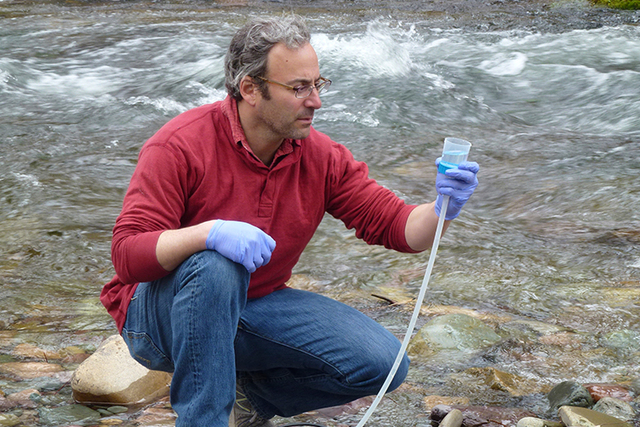 This April 17, 2014 photo provided by the U.S. Forest Service shows Michael K. Schwartz in the process of filtering 5 liters of water to concentrate DNA on a filter to be analyzed at the National  ...