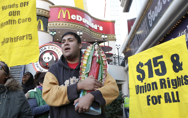Martin Macias-Rivera carries a statue of Virgin Mary as he joined workers fighting for a higher minimum wage protest outside of a McDonald's on Las Vegas Boulevard, Tuesday, Nov. 29, 2016. Bizuaye ...