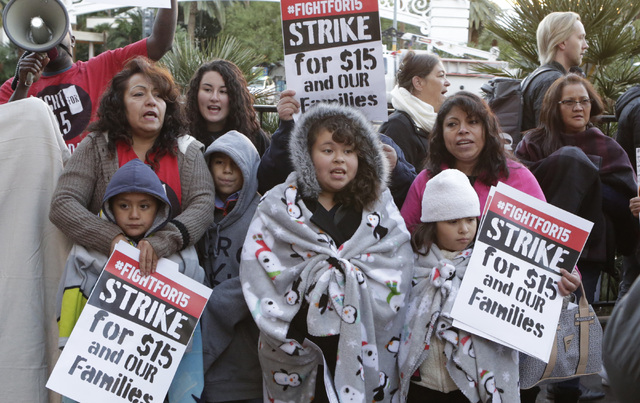 Guadlup Rodriguez, left, and her grandson Nathan Perez, 8 and workers and their families fighting for a higher minimum wage protest outside of a McDonald's on Las Vegas Boulevard, Tuesday, Nov. 29 ...