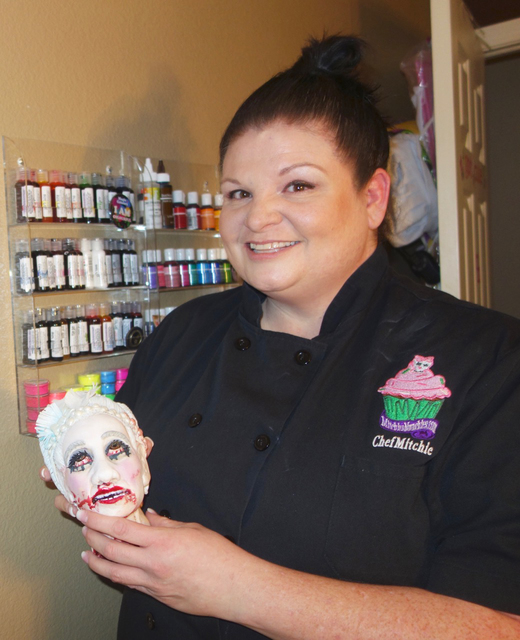 Michelle Curran shows off her version of Marie Antoinette's head, part of a cake she produced for a local Halloween party. The full body was decorated to look like a gown. Included in the presenta ...