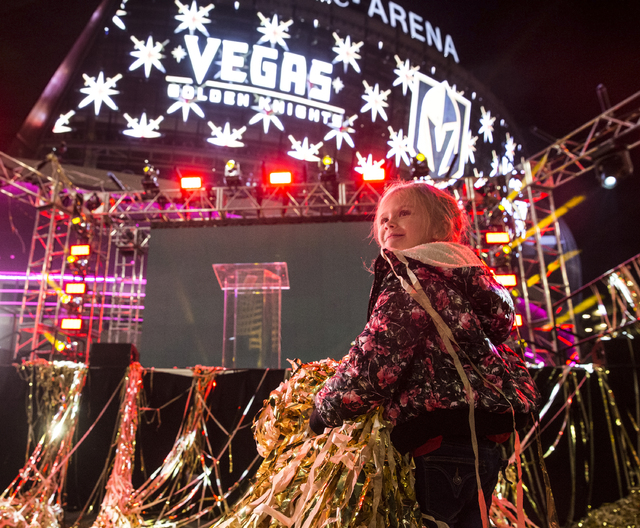 Hannah McKinley plays with gold streamers at the conclusion of a ceremony to unveil the Las Vegas' NHL expansion franchise's official team nickname, logos and colors on Tuesday, Nov. 22, 2016, at  ...
