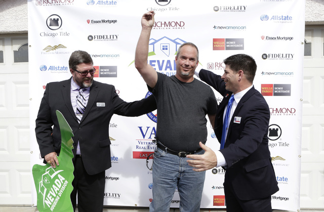 U.S. Army Cpl. Christopher Hudson, center, reacts after receiving the keys to his newly renovated, mortgage-free home in Centennial Hills as Billy Alt, president of the Veterans Association of Rea ...