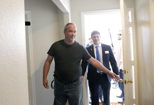 U.S. Army Cpl. Christopher Hudson, left, flanked by Billy Alt, president of the Veterans Association of Real Estate Professionals, right, enters his newly renovated home Oct. 14, 2016, in Las Vega ...