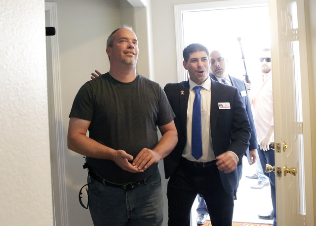 U.S. Army Cpl. Christopher Hudson, left, flanked by Billy Alt, president of the Veterans Association of Real Estate Professionals, right, enters to his newly renovated home Oct. 14, 2016. Bizuayeh ...