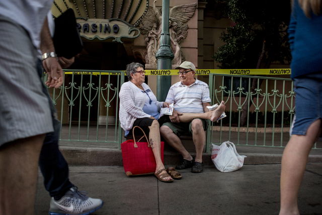 Helene Decary and Jacques Decary, guests of the Paris hotel-casino, sit outside of the establishment while waiting for updates on the power outage on Thursday evening, Nov. 3, 2016 in Las Vegas.   ...