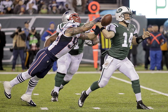 New England Patriots defensive end Chris Long (95) gets a hand on the ball as New York Jets quarterback Ryan Fitzpatrick (14) throws during the fourth quarter of Sunday's game in East Rutherford,  ...