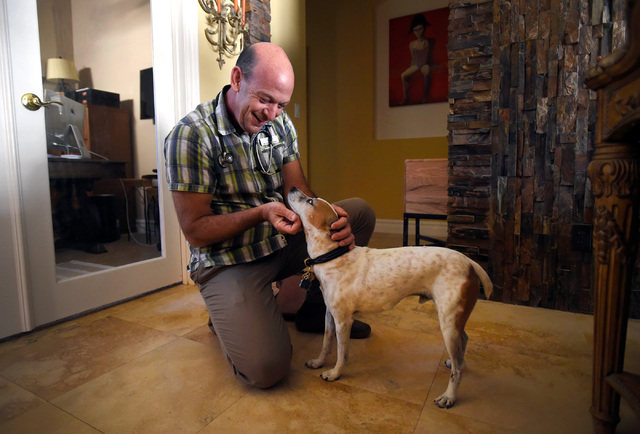 Veterinarian Dr. Toby Goldberg greets his patient, Sammie, a 13-year-old Jack Russel terrier, during a house call at Larry Klecka and Cheryl Mitt's home, Thursday, Oct. 20, 2016, in Las Vegas. The ...