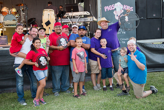 The 2016 Pigs for the Kids' grand champion Team Infinite Smoke BBQ (in purple shirts) and second place team, Rollin Smoke Barbecue, are seen Sept. 17, 2016, at the event held in North Las Vegas.   ...
